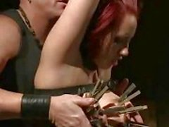 Strapped redhead covered in clothespins