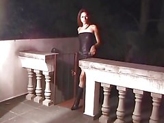 Tranny with long dark hair and small tits sucks on guys dick on the balcony