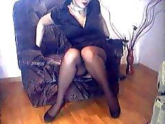fru i nylonstrumpor och höga klackar korsar benen