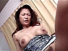 Busty Japanese brunette taking a little sex toy down her snatch