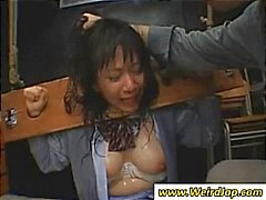 Two Asian chicks put in head and arm restraints and face fucked by force