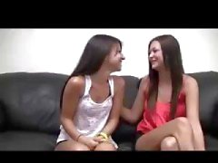 Duas garotas lésbicas morena bate-papo no sofá antes de jogar uns com os outros