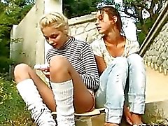 Two chicks trying dildos outdoors