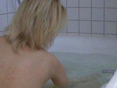 Tattooed blonde bathing and teasing naked