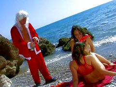 French Santa looks for reindeer on beach
