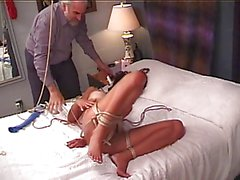 Hot young brunette gets her nipples, pussy clamped while bound on the bed