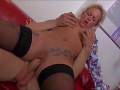 Blonde Hausfrau auf dem Sofa gevoegelt
