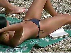 Adolescente magro com peitos empinados nus em uma praia de nudismo