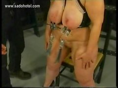 Fat milf slave gets metal clamps on her large tits by masked master in a dungeon bdsm