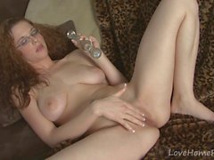 Busty redhead with glasses masturbating on a couch