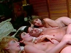 Blonde bitch Nina Hartley is naked in bed with her girlfriends