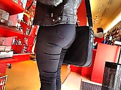 Gal with a big butt is standing in the store looking caught