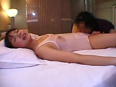 Pigtailed Asian cutie lies on the bed and gets her wet puss