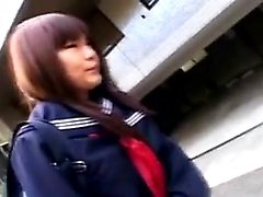 Cute Asian schoolgirl sits on the toilet and makes herself