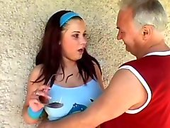Busty girl with old guy on the footbal field.