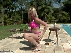 Blonde tranny oils herself up outdoors by the pool and jerks