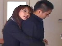 Asian teacher and teen caress in a class-room