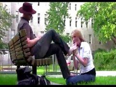 Submissive girl licks man&#039_s feet in park