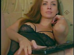Long-haired brunette with nice tits strokes her pussy throu