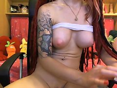 Tattooed redhead with big tits fingers her hairless snatch