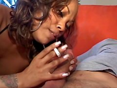 Cute black slut with nice tits and a tattoo sucks cock while smoking her cig