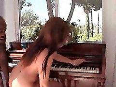 Kinky tramp sucking black cock on the piano