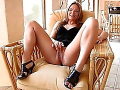 Carolyn cute blonde with long hair and natural tits toying pussy in armchair