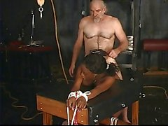 Busty black slave is roped to the ground and has to suck her master's big cock