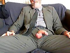 le papa barbue sexy après la combinaison de travail et l'allègement de la cravate sur le canapé