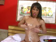 Petite shemale in thongs spreads lotion over her sexy body