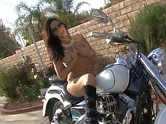 Gorgeous brunette babe fucks her juicy cunt with her favorite sex toy on a motorbike
