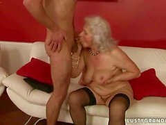 Horny boy fucking a busty granny on couch