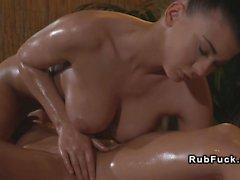 Busty masseuse rubs pussy