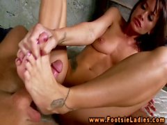 Footworshipping babe massages hard cock