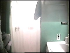 A spycam in the bathroom captures a hot brunette getting na