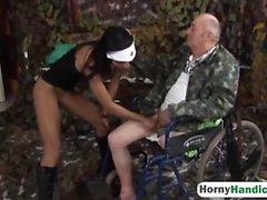 Beautiful tonåring sjuksköterska monterar amputerad person morfadern in rullstolsanpassad