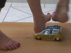 Girls crushing little toy car barefoot