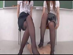 Two luscious Oriental gals stroke his dick and give a pantyhose covered footjob