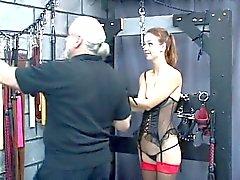 Esclavos atractiva joven consigue con los brazos acotada superiormente cabeza y trae un castigo
