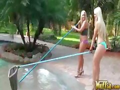 Two blonde babes are out by the pool cleaning and eating pussy