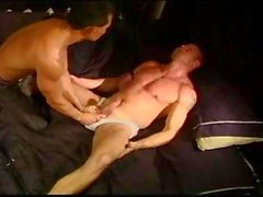 CBT Hot hung smooth muscle stud has balls punched and squeezed by another hot smooth muscle stud.