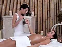 Brunette lesbian on massage table gets oiled