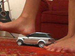 2 girls crushing silver toy car barefoot
