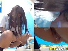 Asiático adolescente orina en el baño