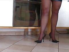 Trevlig kvinna i tätt läderklänning Höga klackar och stövlar