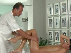 Brunette gives footjob to her masseur