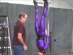 suspended in purple catsuit
