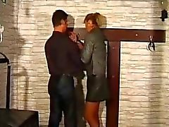 Mature Woman Getting Tied To Cross Spanked With Stick Getting Her Tits Rubbed By Master In The Dungeon