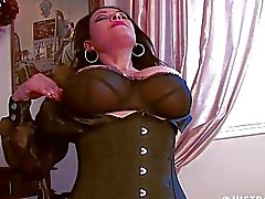 Arousing brunette momma in corset and stockings shows her pussy