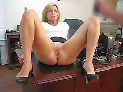 Rijpe blonde secretaresse spreidt haar benen en masturbeert op het bureau